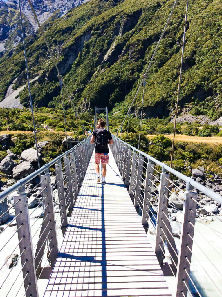 walking over metal suspension bridge in new zealand
