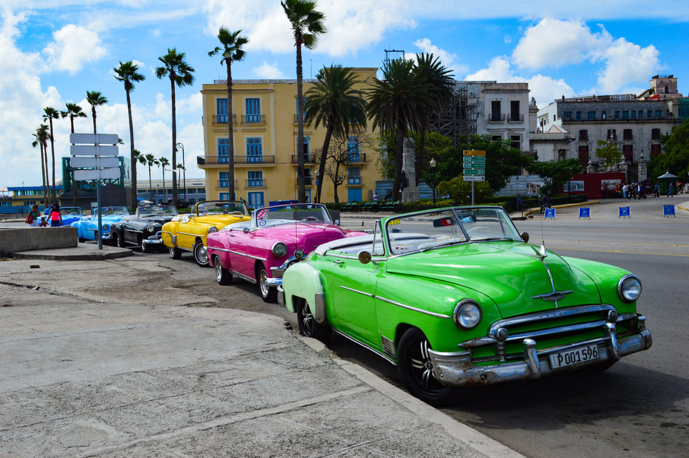 green pink and blur convertible cars lined up in Havana
