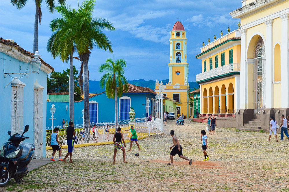 kids playing football on cobbles in front of brightly painted buildings