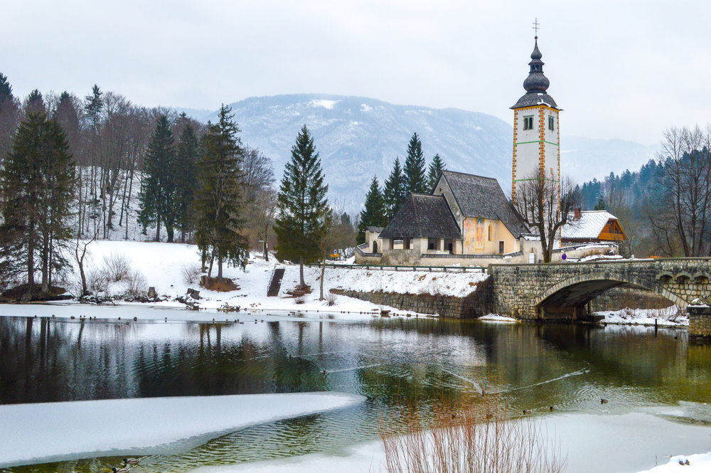 frozen stream with church and pine trees