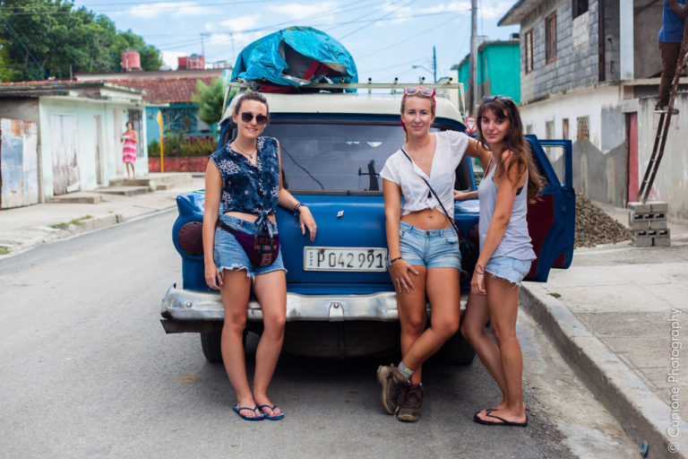 girls posing in front of vintage car in Cuba