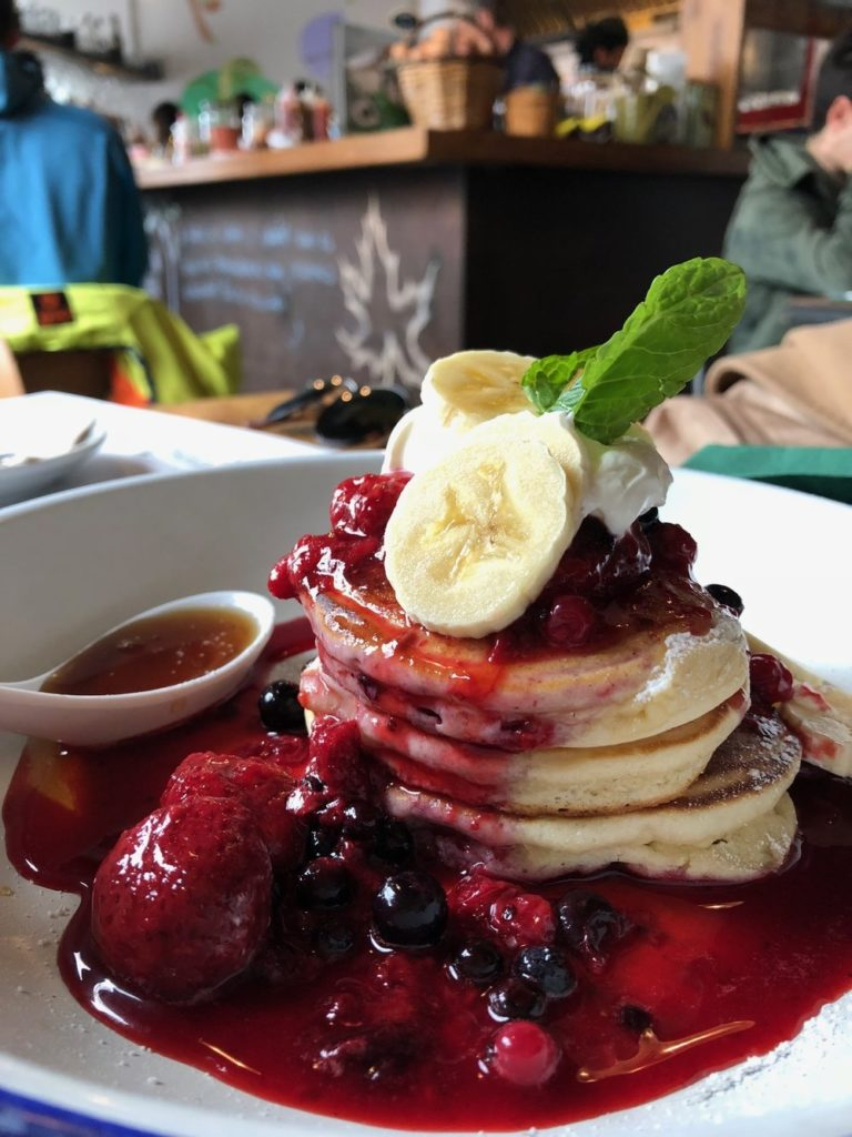 stack of pancakes with fruit coulis