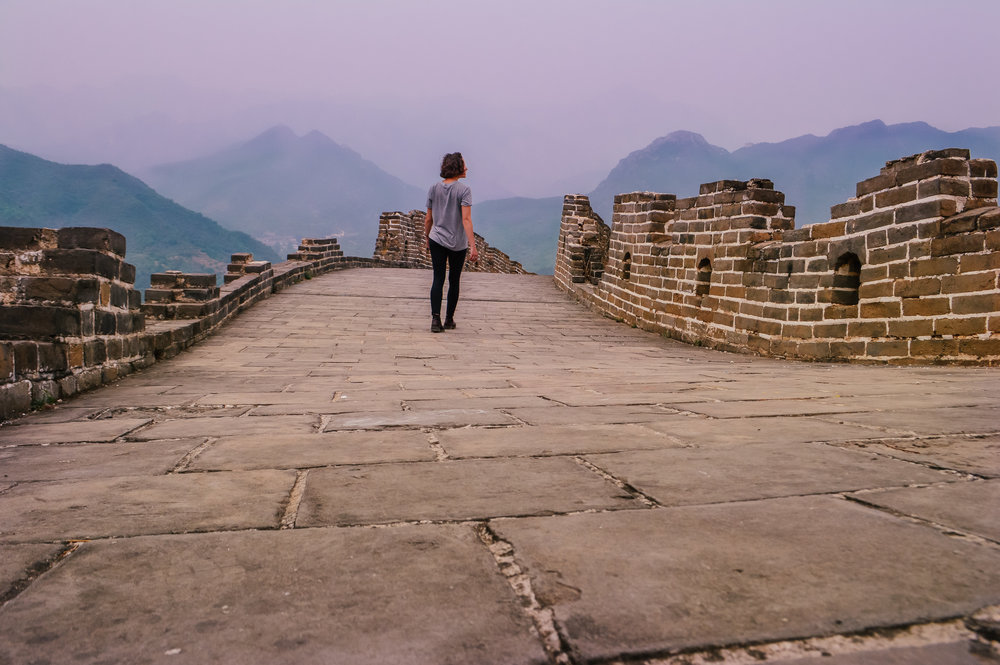 girl walking on great wall of china at sunset