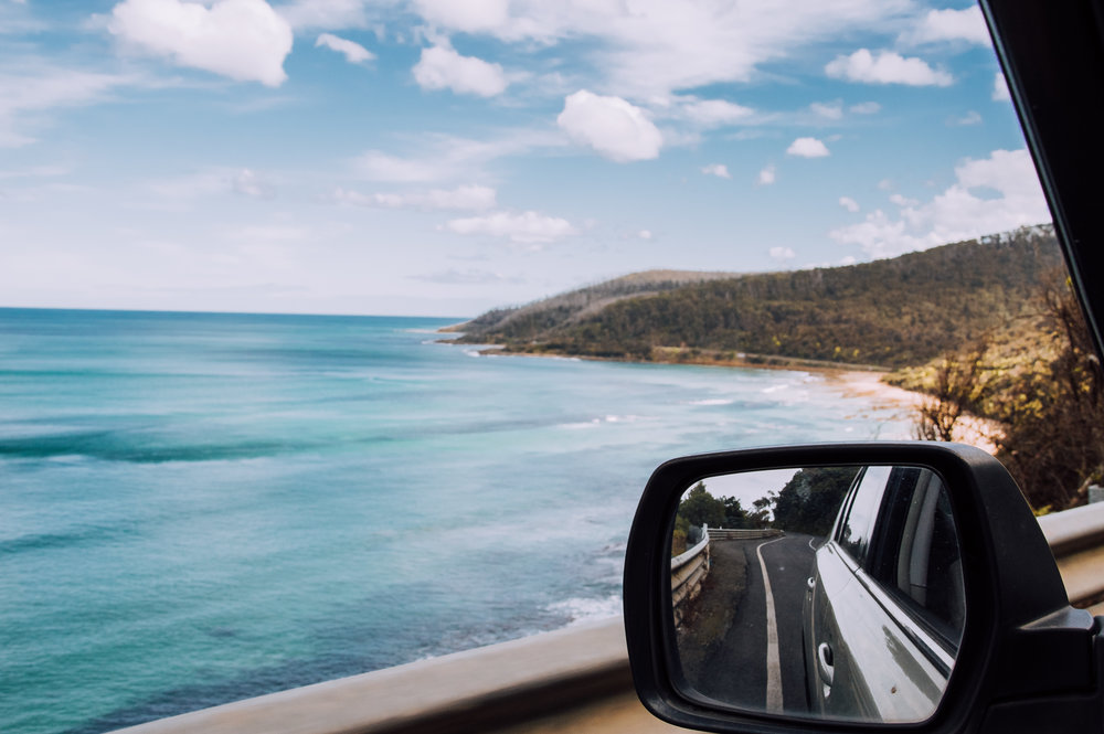 looking out the window of the car with wing mirror and sea