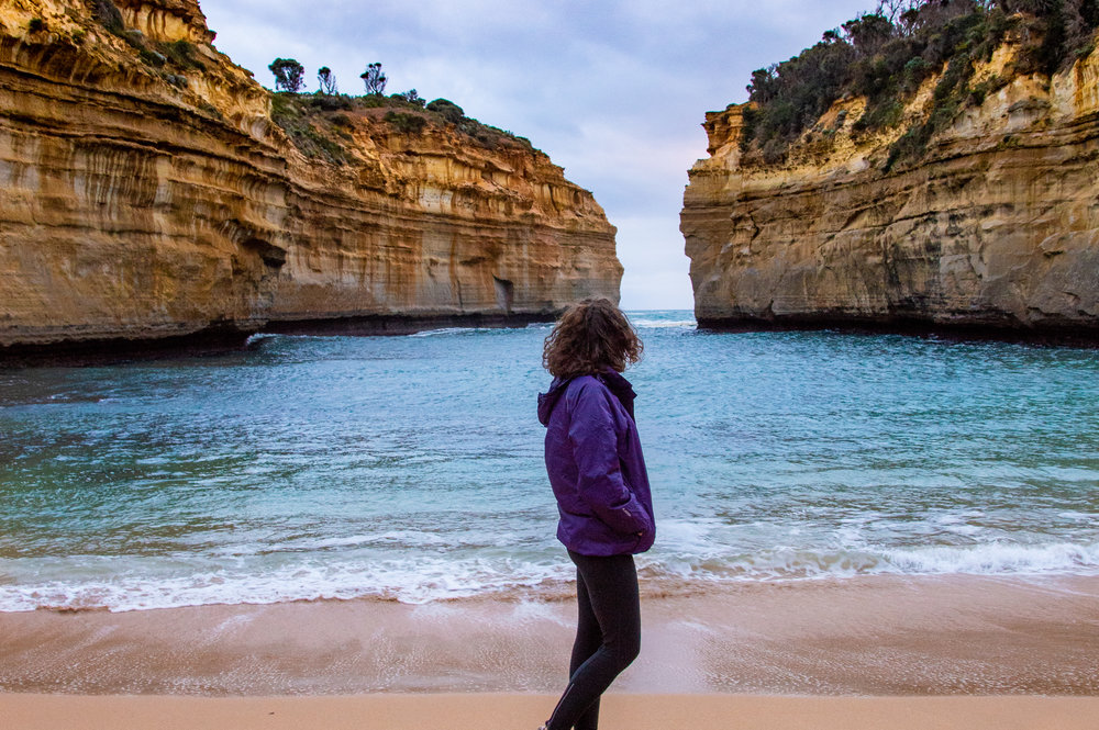 girl in purple waterproof looking out towards the sea and cliffs