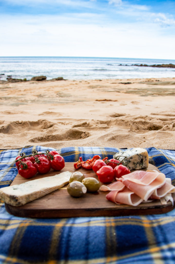 charcuterie platter on a blue mat on the beach