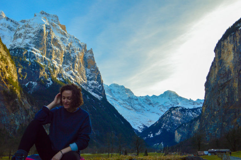 girl sat on a rock with swiss mountains