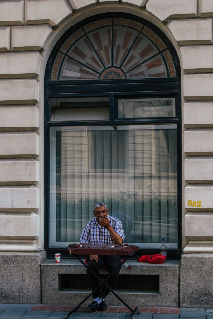 man busking on the street of bucharest in front of large window