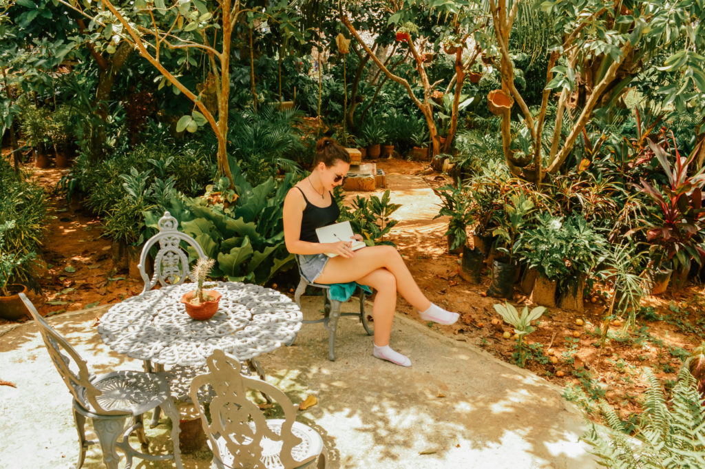 girl sat in jungle garden writing in a journal