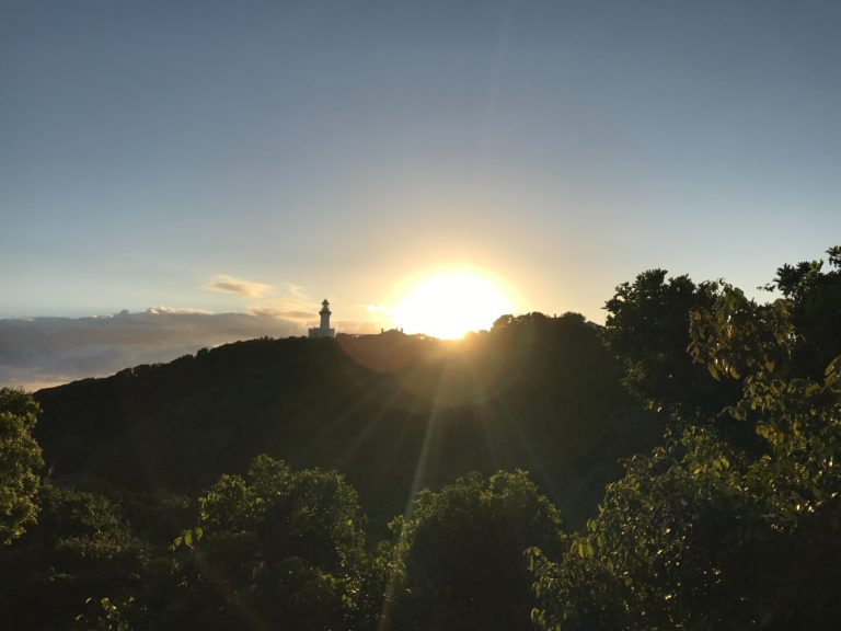 byron bay at sunset with lighthouse in distance