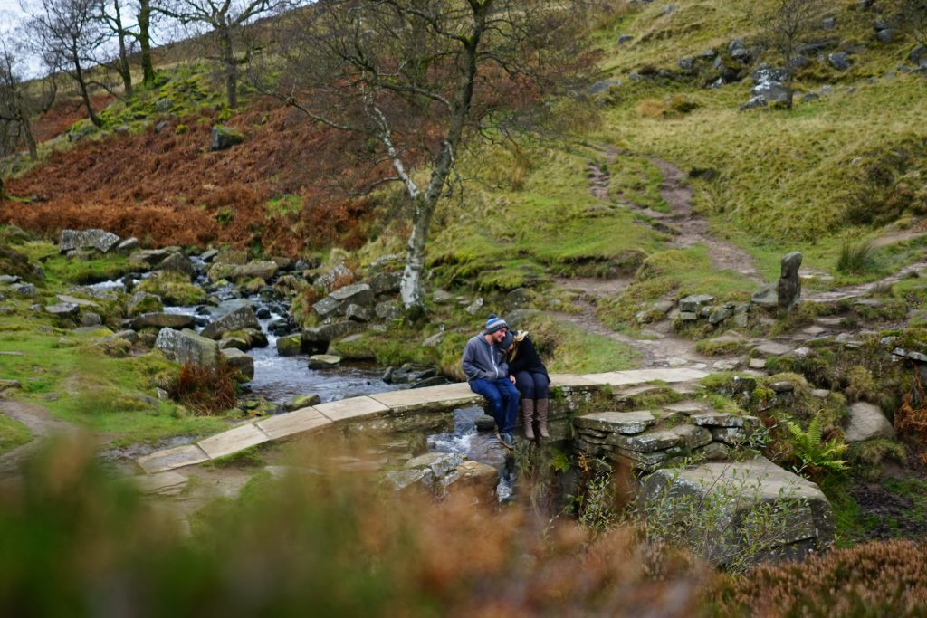 Couple sat on bridge with stream and green hills in Haworth