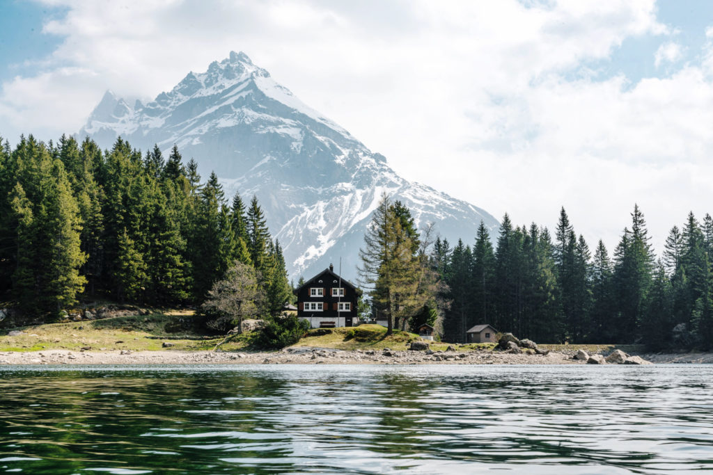 swiss house on lakefront surrounded by trees and a mountain