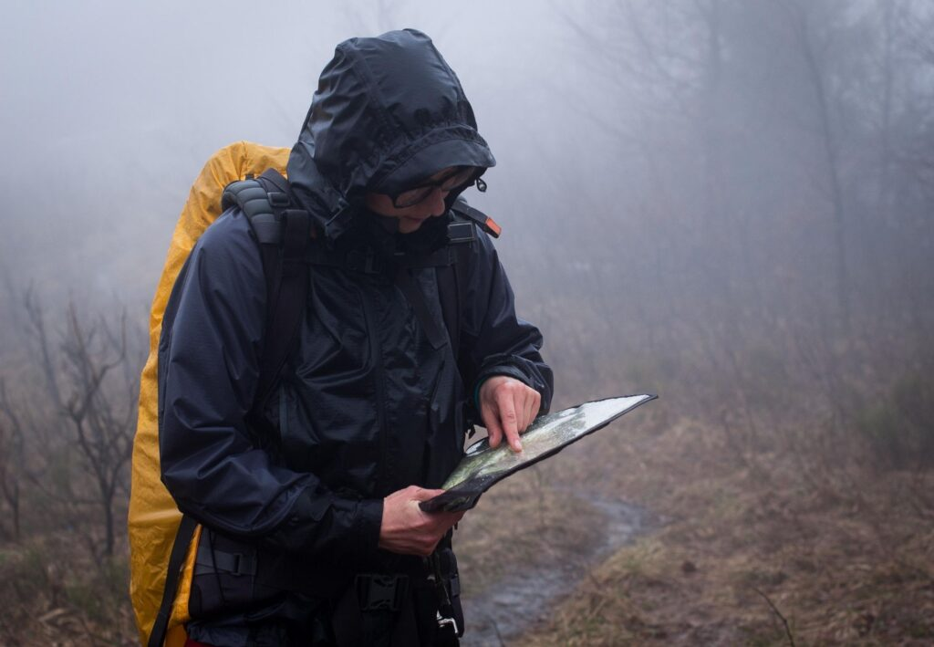 girl in bad weather looking at map in the rain