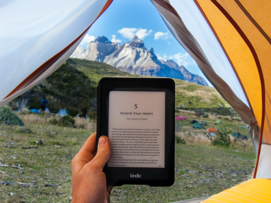 hand holding kindle in tent with mountain backdrop