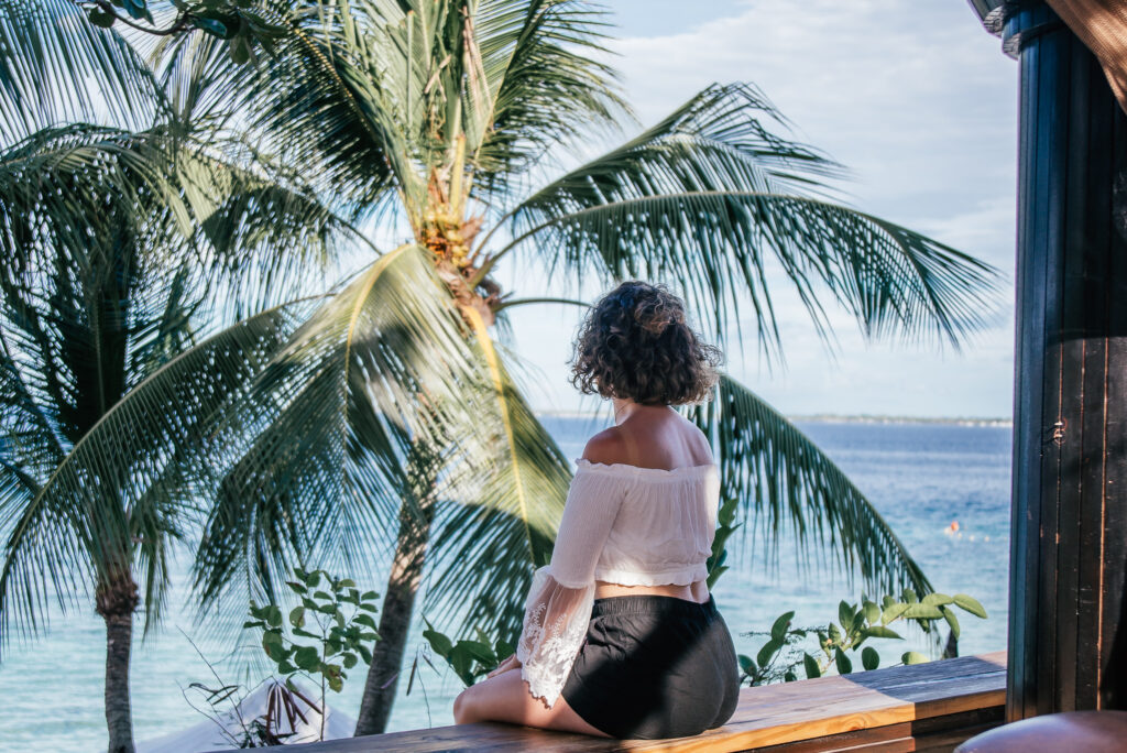 girl sat on bench in front of sea and palm trees in a resort