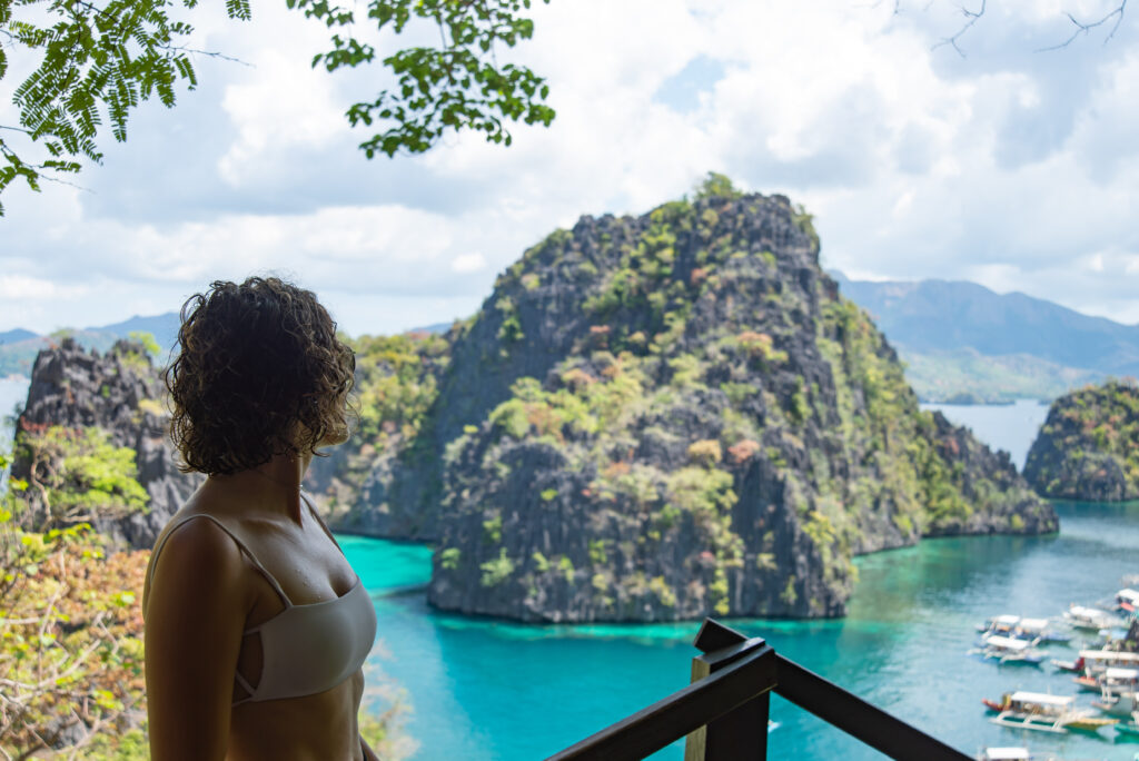 girl in bikini looking out to islands from a view point in Coron