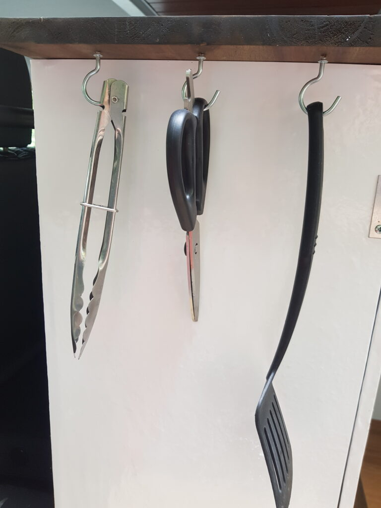 white cupboard with cooking utensils hanging from hooks