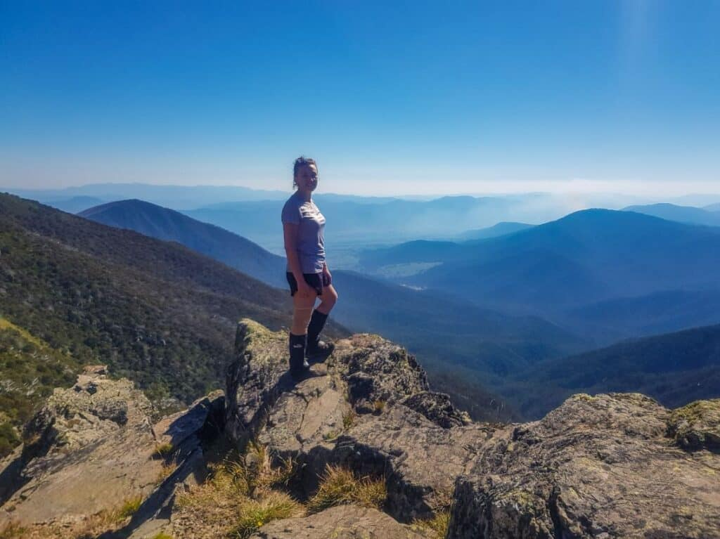 girl standing on a rock with a mountain backdrop in the Alpine National Park