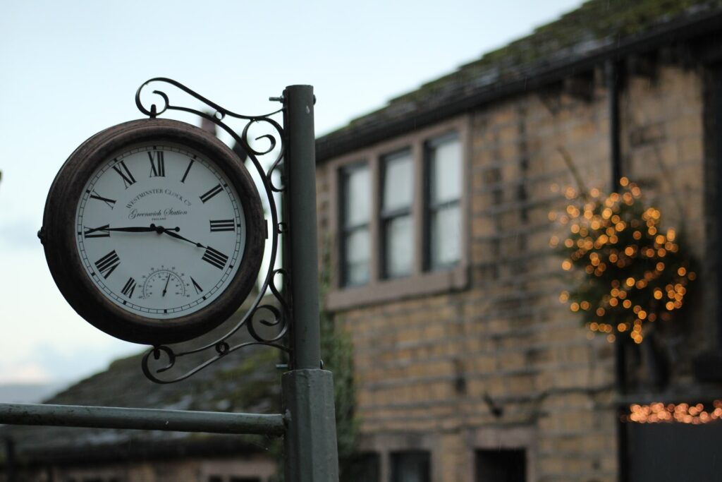 close up of a clock with stone building behind