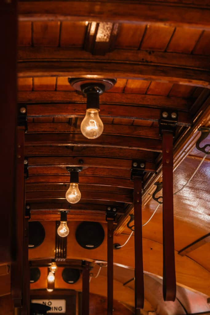 hanging lightbulbs on a wooden ceiling in a vintage tram carriage