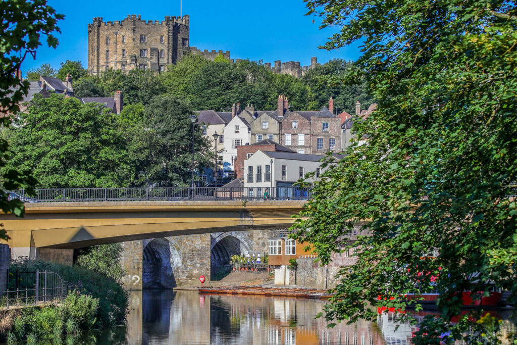 bridge over river with castle and framed by green trees