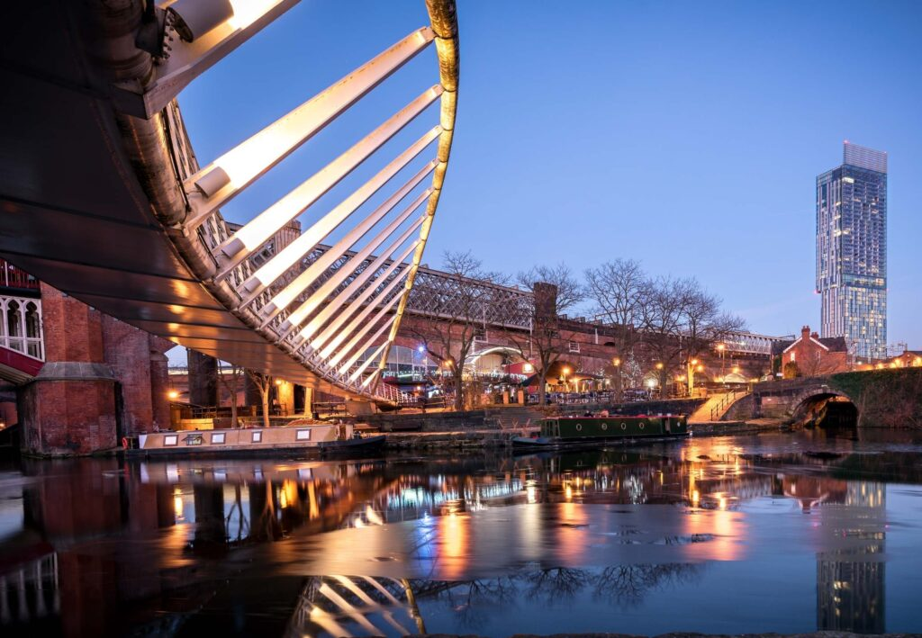 modern curved bridge and quayside in manchester at night with lights reflected in the water